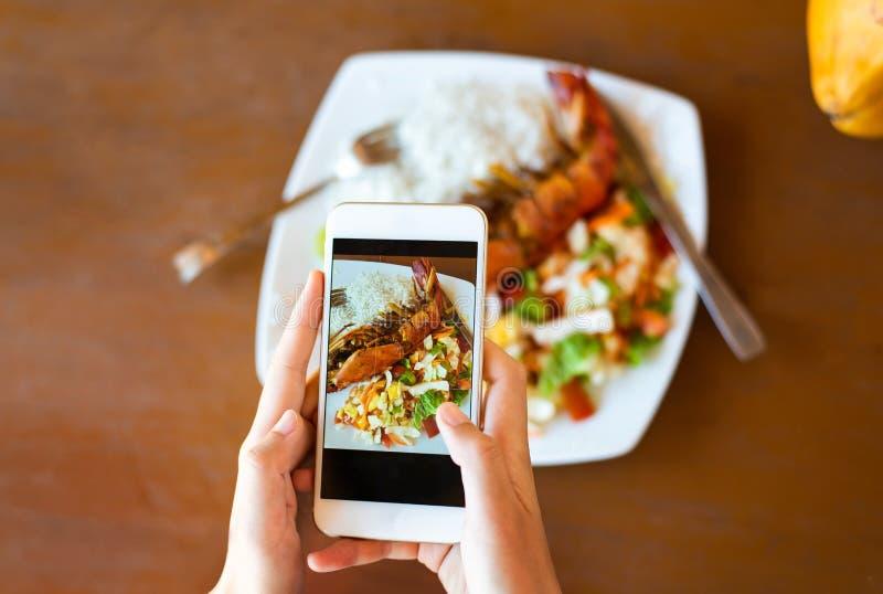 Meisje die foto van zeevruchten in een restaurant nemen stock afbeelding