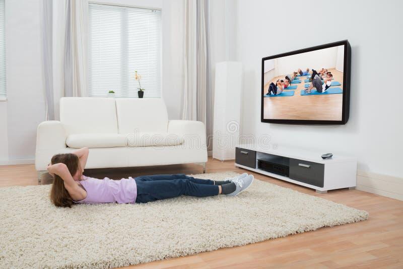 Meisje die in Front Of Television uitoefenen royalty-vrije stock foto's