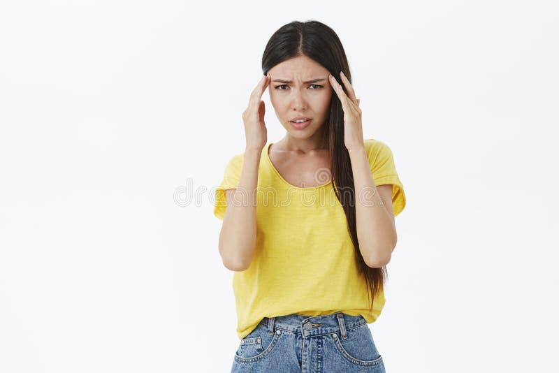 Meisje die gek met het hoofd rond spinnen gaan Unfocused en verward gefrustreerd gelooid wijfje in gele t-shirtholding stock fotografie