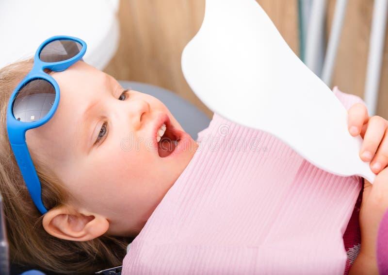 Meisje die genezen tanden door de spiegel in pediatrische tandkliniek bekijken stock fotografie