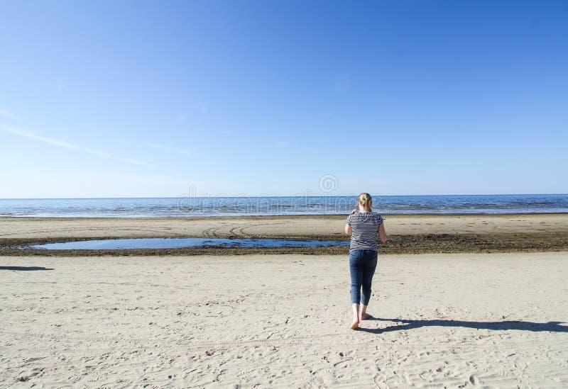 Meisje die in gestreepte kort en jeans op Oostzeekust lopen stock fotografie