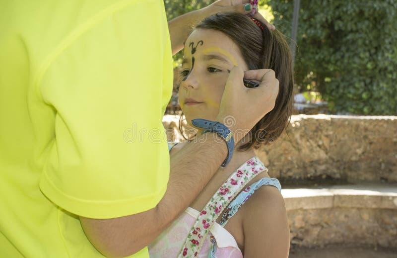 Meisje die gezicht krijgen die tijdens in openlucht partij wordt geschilderd stock fotografie