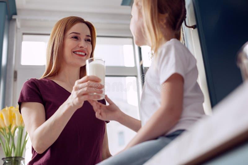 Meisje die glas melk van moedershanden nemen royalty-vrije stock afbeeldingen