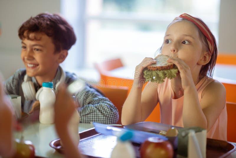 Meisje die grappig gezicht maken terwijl het eten van yummy sandwich royalty-vrije stock foto