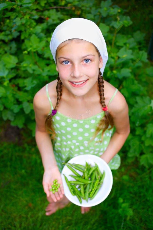Meisje die groene Erwten houden stock afbeelding