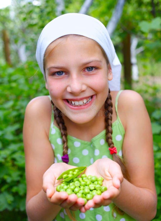 Meisje die groene Erwten houden stock foto