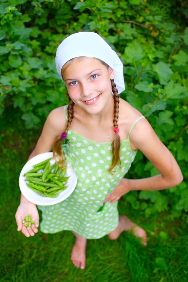 Meisje die groene Erwten houden royalty-vrije stock fotografie