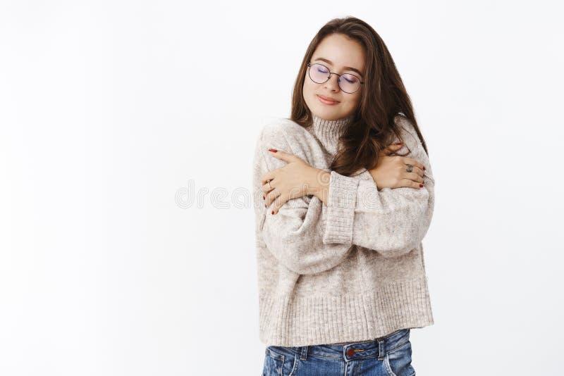 Meisje die groot in zachte comfortabele sweater tijdens koel weer die koesteren en van comfort en verrukking dicht glimlachen voe stock fotografie