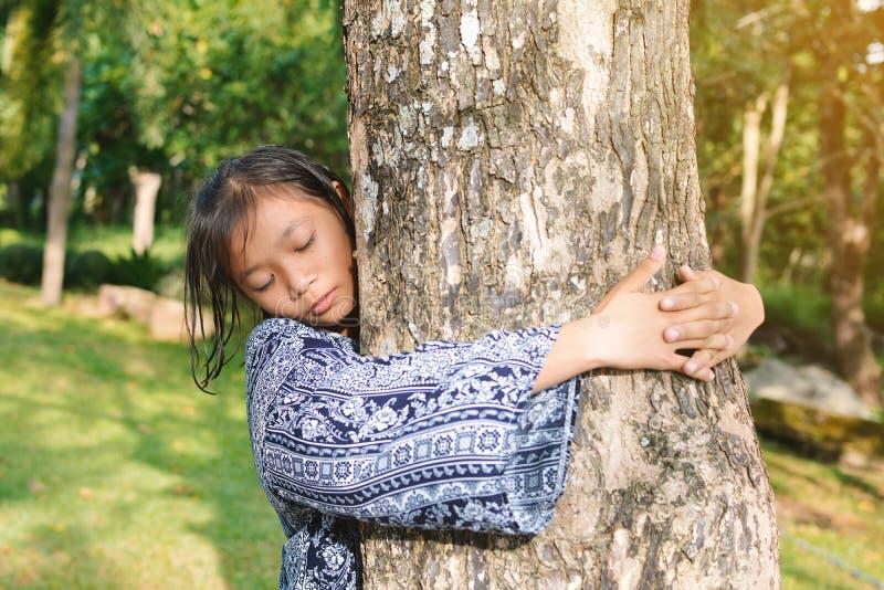 Meisje die grote boom koesteren stock foto