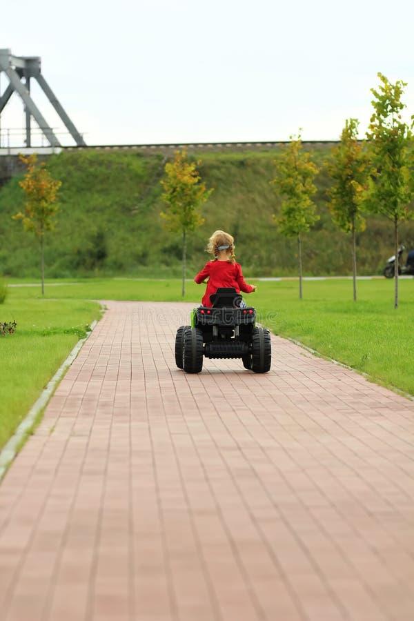 Meisje die grote stuk speelgoed auto in park berijden royalty-vrije stock fotografie