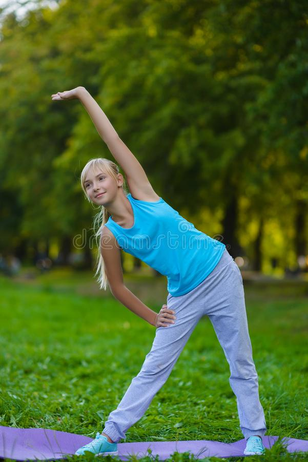 Meisje die gymnastiek- oefeningen of uitoefenen doen openlucht stock afbeeldingen