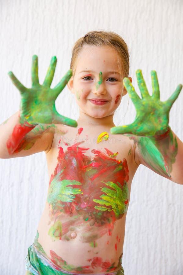 Meisje die haar die handen tonen, in vingerverf worden behandeld stock fotografie