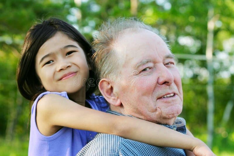 Meisje die haar grootvader koesteren in openlucht, diversiteit stock afbeelding