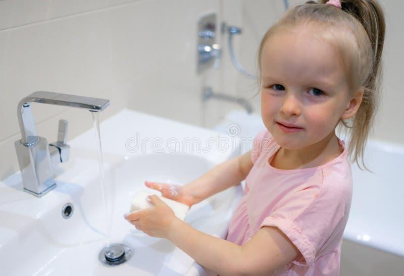 Meisje die haar handen met zeep wassen stock foto