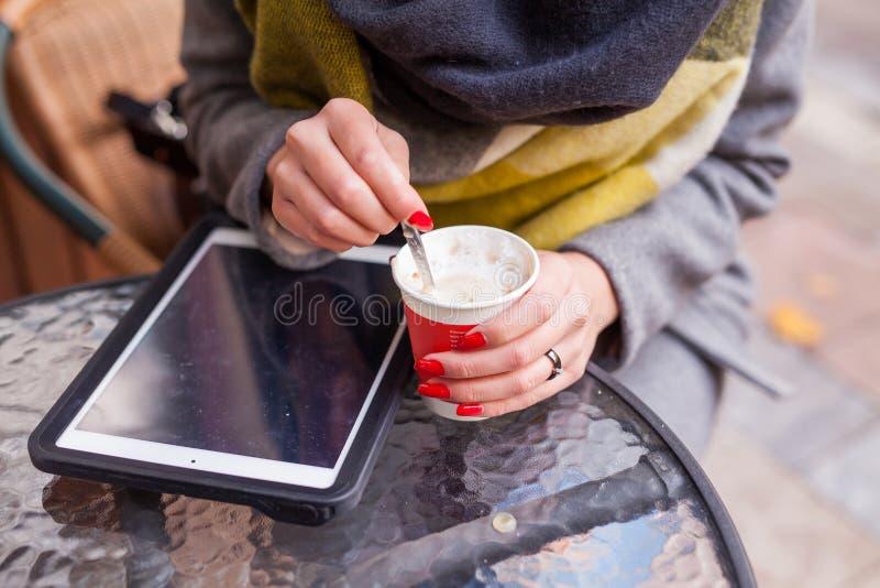 Meisje die haar koffie in het park stiring Tabletpc op de lijst clo royalty-vrije stock foto's