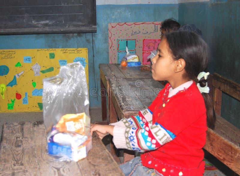 Meisje die haar maaltijd eten op school in een het kamperen reis in Egypte stock foto's