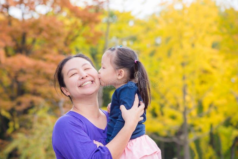 Meisje die haar moeder in de herfstpark kussen stock foto's