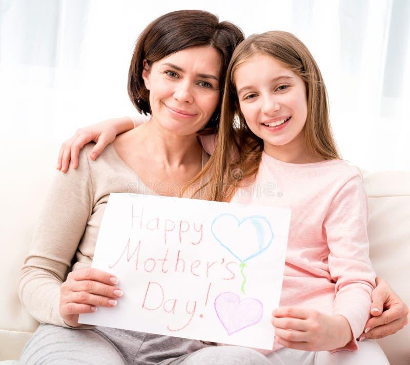 Meisje die haar moeder koesteren en greating kaart houden royalty-vrije stock afbeelding