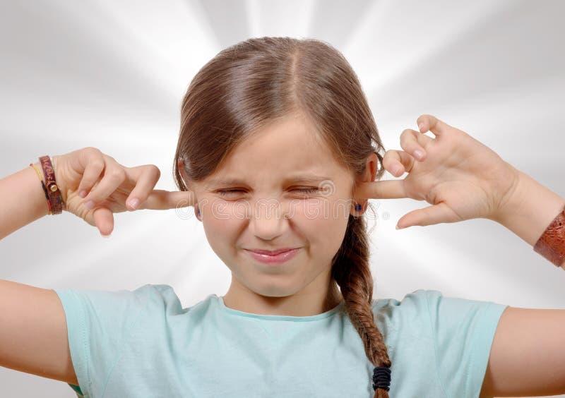 Meisje die haar oren behandelen, om einde te zeggen die hevig lawaai maken die me geven stock foto