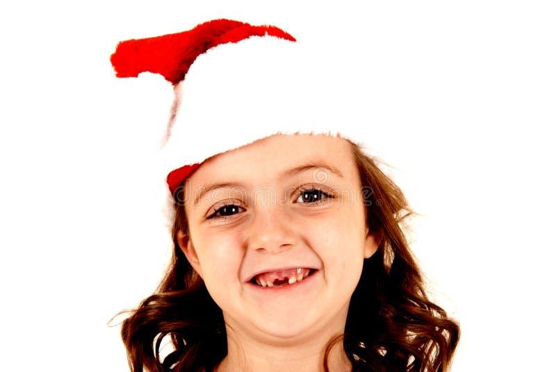 Meisje die haar twee voortanden missen die santahoed dragen royalty-vrije stock fotografie