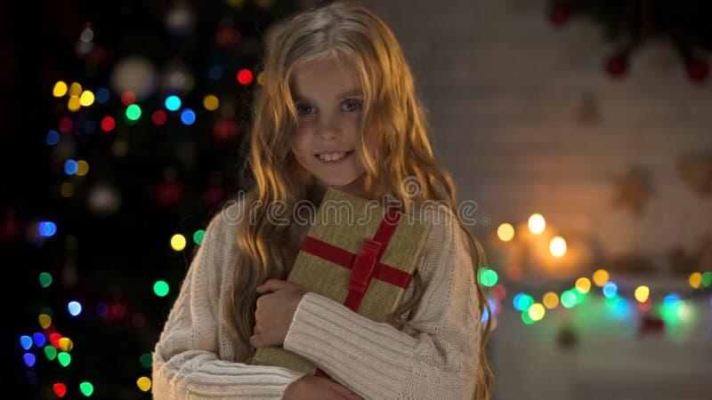Meisje die heden koesteren dichtbij Kerstmisboom en bij camera, de wintersprookje glimlachen stock fotografie
