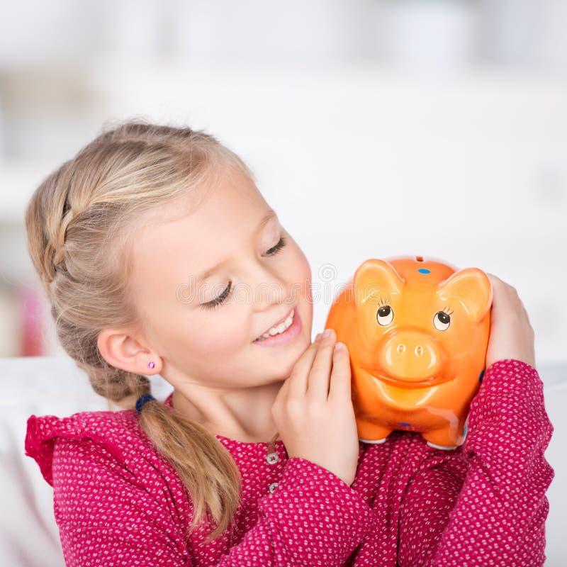 Meisje die het glimlachen van het spaarvarken bekijken royalty-vrije stock afbeelding