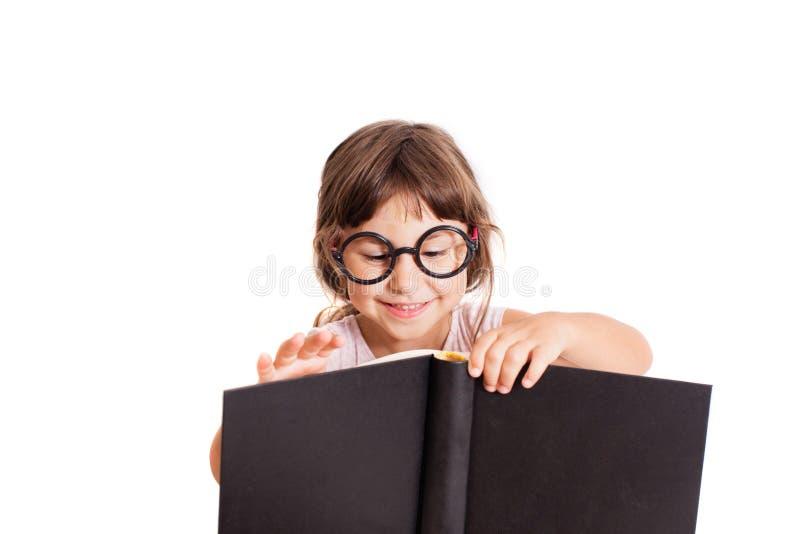 Meisje die het grote boek bekijken stock foto's