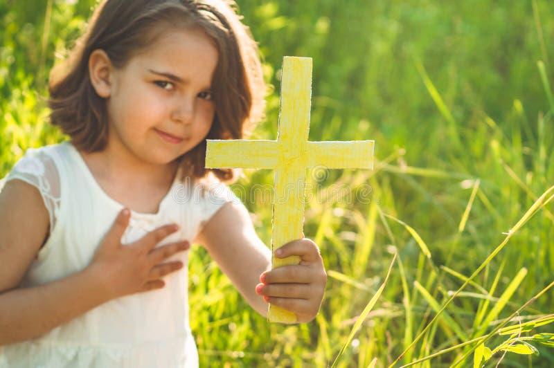 Meisje die het kruis in hand tijdens mooie zonsondergang houden Handen die in gebedconcept worden gevouwen voor geloof stock foto