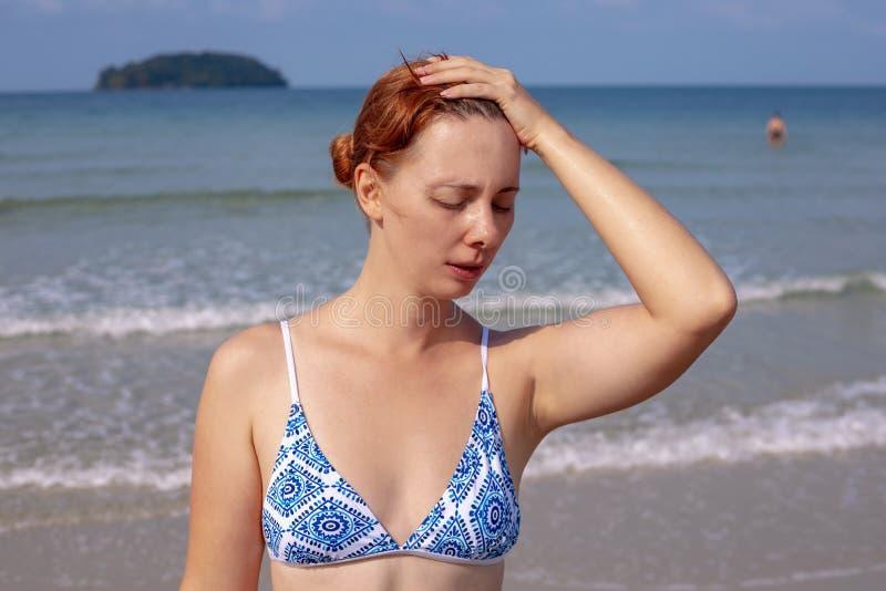 Meisje die hoofdpijn op kust hebben Het lijden van aan vrouw op zonnig strand Vrouwenzonnesteek door overzees Heet zongevaar royalty-vrije stock foto