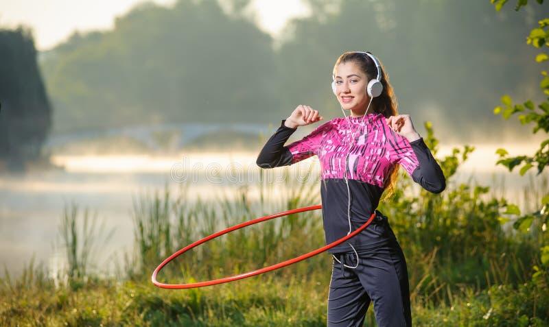 Meisje die hulahoepel doen in openlucht dichtbij het meer stock foto