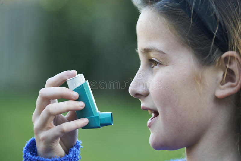 Meisje die Inhaleertoestel met behulp van om Astmaaanval te behandelen stock afbeelding