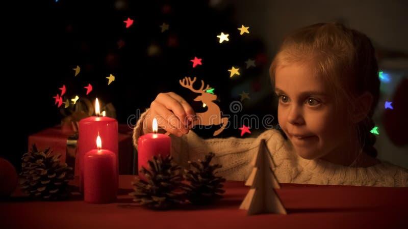 Meisje die Kerstman veronderstellen die op houten herten vliegen, die met Kerstmisdecoratie spelen stock foto