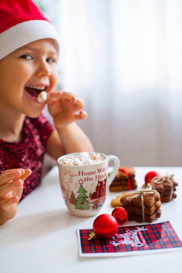 Meisje die in Kerstmanhoed heemst van mok met cacao en koekjes, Vrolijke Cristmas eten stock fotografie
