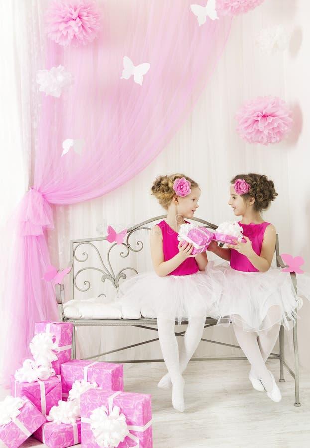 Meisje die kinderenverjaardagsgeschenk geven aan zuster De dozen van de jonge geitjesgift stock afbeelding