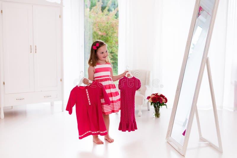 Meisje die kleding in witte slaapkamer kiezen royalty-vrije stock fotografie