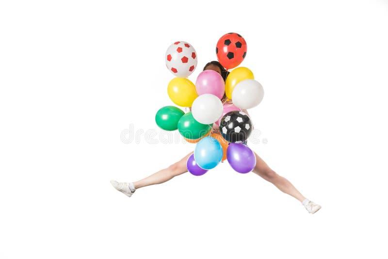 meisje die kleurrijke ballons en het springen houden royalty-vrije stock afbeelding