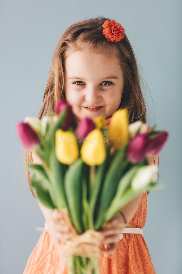 Meisje die kleurrijke bloemen geven, die oprecht glimlachen royalty-vrije stock fotografie