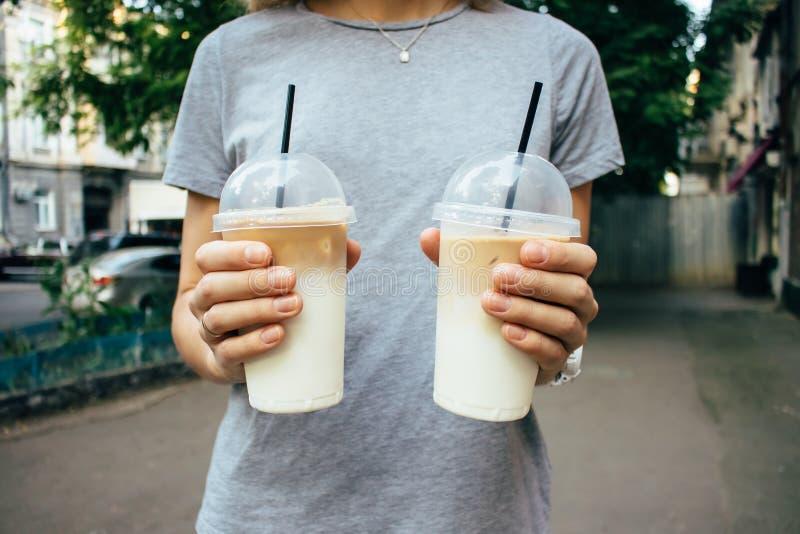 Meisje die koffie twee lattes in plastic transparante koppen houden stock afbeelding