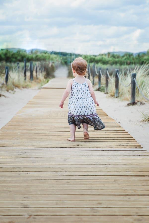 meisje die langs een houten gang op het strand in de zomer lopen royalty-vrije stock afbeelding
