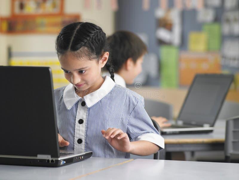 Meisje die Laptop in Klasse met behulp van stock afbeeldingen