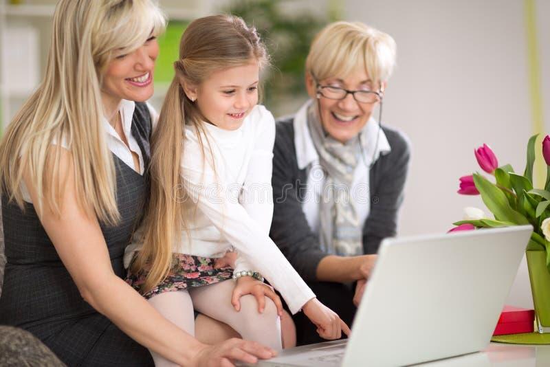 Meisje die laptop met moeder en grootmoeder met behulp van royalty-vrije stock foto