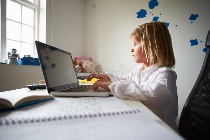 Meisje die Laptop in Slaapkamer met behulp van stock afbeelding
