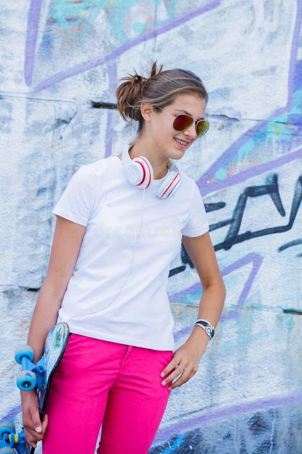 Meisje die lege witte t-shirt, jeans dragen die tegen ruwe straatmuur stellen royalty-vrije stock foto's