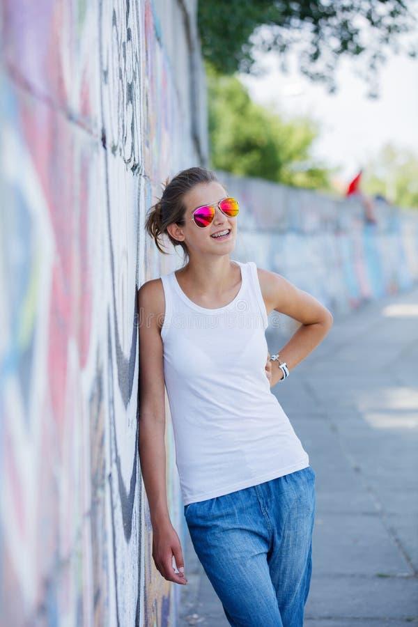 Meisje die lege witte t-shirt, jeans dragen die tegen ruwe straatmuur stellen royalty-vrije stock foto