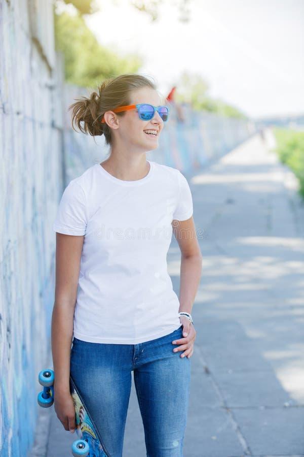Meisje die lege witte t-shirt, jeans dragen die tegen ruwe straatmuur stellen stock foto