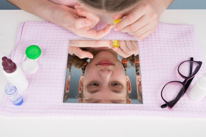 Meisje die lenzen voor betere visie, bezinning in de spiegel voorbereidingen treffen te dragen royalty-vrije stock foto