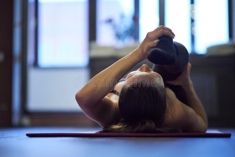 Meisje die lichaamsbeweging doen en benen op een mat, voet uitrekken dicht omhoog, gezond levensstijlconcept Zijaanzicht van stock foto's