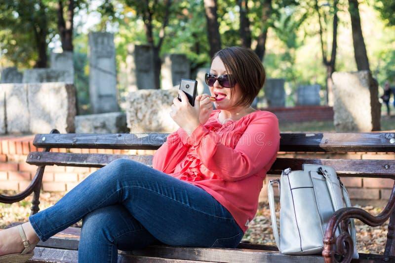 Meisje die Lippenstift op Haar Lippen zetten en Cellphone het gebruiken weerspiegelt in plaats daarvan stock afbeeldingen