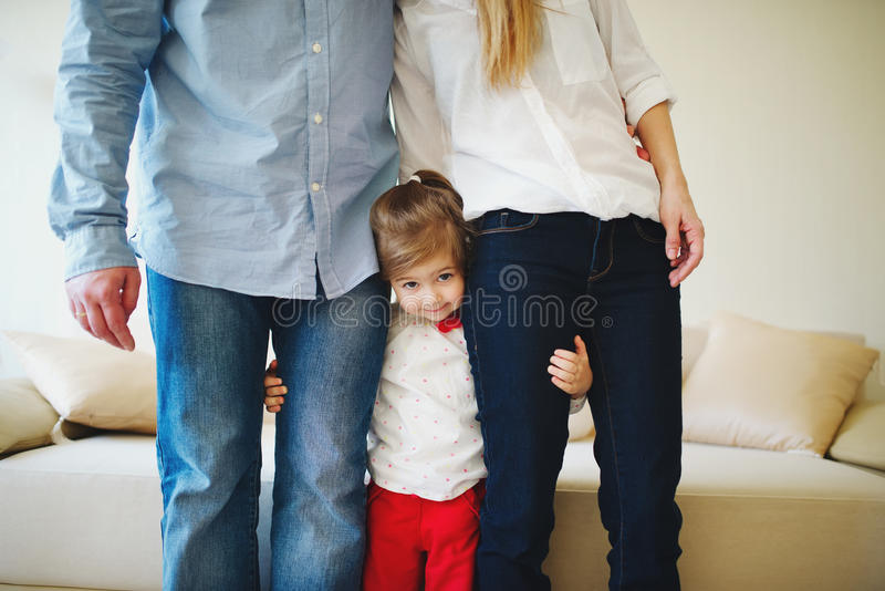 Meisje die mamma en papa voor benen koesteren stock afbeeldingen