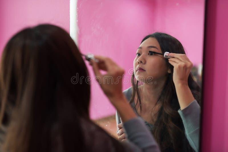 meisje die mascara toepassen op wimpers stock foto's